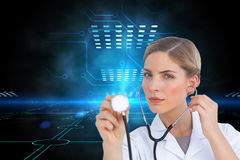 Serious nurse listening with stethoscope Stock Photo