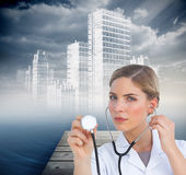 Serious nurse listening with stethoscope Royalty Free Stock Image