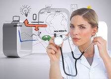 Serious nurse listening with stethoscope Stock Photography