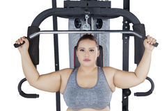 Serious obese female with a cable machine Royalty Free Stock Photos