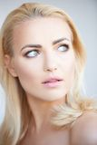 Serious observant young blond woman. With bare shoulders turning to look back over her shoulder with parted lips Stock Photography