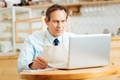 Serious occupied man using the laptop and making notices. Stock Photos