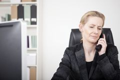 Serious Office Woman Chatting to Someone on Phone. Close up Serious Blond Office Woman at her Office Chatting to Someone on Telephone While Looking Down Royalty Free Stock Image
