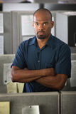 Serious Office Worker. Serious Black man in a cubicle folds his arms Royalty Free Stock Image