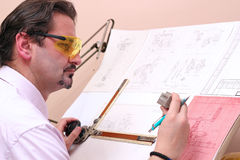 Serious Office Worker - Engineer. Mechanical engineer analyze his design Stock Images