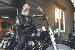 Serious old bearded man on motorcycle Royalty Free Stock Image