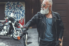 Serious old biker near garage. Confident aged male person in leather clothes is looking aside with concern. He putting palm on handle of motorbike. Portrait stock photos
