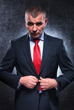 Serious old business man unbuttoning his suit Royalty Free Stock Photography