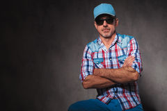 Serious old casual man wearing sunglasses and baseball hat sitti Royalty Free Stock Image