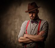 Serious old-fashioned man with hat wearing suspenders and bow tie, posing on dark  background. Royalty Free Stock Photos
