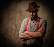 Serious old-fashioned man with hat wearing suspenders and bow tie, posing on dark  background. Serious old-fashioned man with hat wearing suspenders and bow tie Royalty Free Stock Photo