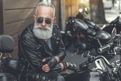 Serious old male person using motorbike Royalty Free Stock Photo