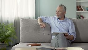 Serious old male sitting on sofa and reading news on tablet, modern technologies. Stock footage stock video footage