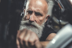 Serious old man doing renovation of bike. Confident mature bearded biker is repairing his motorbike. Focus on male concentrated face. Portrait. Close up Stock Image
