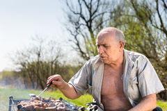 Serious Old Man Grilling at the Camp Area Royalty Free Stock Photography