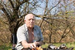 Serious Old Man Roasting Sausage at Camp Area Stock Photo
