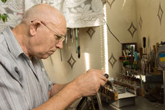 Serious Old Man Working For Electronic Device Stock Images