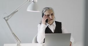 A serious old woman with gray hair and deep wrinkles is talking on a mobile phone in an office. Grandma works with a laptop indoors stock video footage