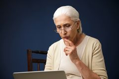 Serious old woman using laptop computer. Looking aside. Image of serious old woman sitting over dark blue background using laptop computer. Looking aside Royalty Free Stock Photography