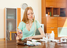 Serious ordinary woman counting the cost of treatment Stock Photos