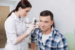Serious otolaryngologist examining ear of male patient Royalty Free Stock Photo