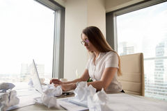 Serious overwhelmed businesswoman working on laptop surrounded b royalty free stock photos