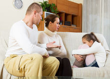 Serious parents scolding daughter in home stock photos