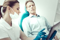 Serious patient listening to his dentists explanations Royalty Free Stock Photo