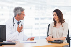 Serious patient talking with her doctor about illness Stock Photo