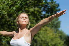 Serious peaceful woman doing yoga in a park Royalty Free Stock Photo
