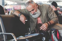 Serious pensioner laying volume in luggage stock photo