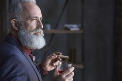 Serious pensioner tasting alcohol and keeping tobacco Royalty Free Stock Image