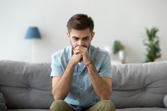 Serious pensive man sitting thinking at home royalty free stock image