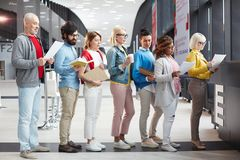 Registration for business forum. Serious pensive people in casual clothing reading application form while standing in line while going to apply request royalty free stock image