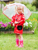 Serious pensive pretty little girl in red raincoat with umbrella Royalty Free Stock Images