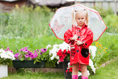 Serious pensive pretty little girl in red raincoat with umbrella Stock Image