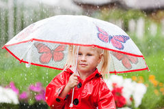 Serious pensive pretty little girl in red raincoat with umbrella Stock Photos