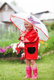 Serious pensive pretty little girl in red raincoat with umbrella Royalty Free Stock Photography