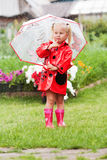 Serious pensive pretty little girl in red raincoat with umbrella Stock Images