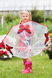 Serious pensive pretty little girl in red raincoat with umbrella walking in park summer Royalty Free Stock Photos