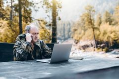 Adult gamekeeper with laptop and smartphone. Serious pensive senior entrepreneur in work overalls is having a phone conversation while sitting at the wooden Stock Image