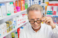 Serious pharmacist holding his glasses Stock Photography