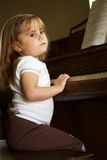 A serious piano player. A little girl seriously playing the piano Royalty Free Stock Photography