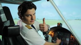 Serious pilot making thumbs up gesture at camera, recommending reliable airline. Stock footage stock footage