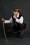 Serious pirate with sabre sitting Stock Photos