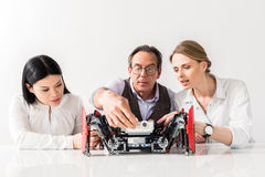 Serious pleasant colleagues working together. Scrutinize in details. Portrait of concentrated professional engineers are looking at robot with interest while Stock Images