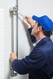Serious plumber repairing shower head Stock Photography