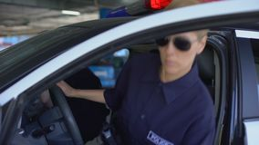 Serious police officers getting into car, ready to start shift, law and order. Stock footage stock video