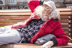Serious poor man lying on the bench. Comfortable place. Serious poor man lying on the bench while feeling comfortable there royalty free stock photos