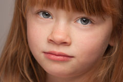 Serious Portrait of an Adorable Red Haired Girl on Grey Stock Image